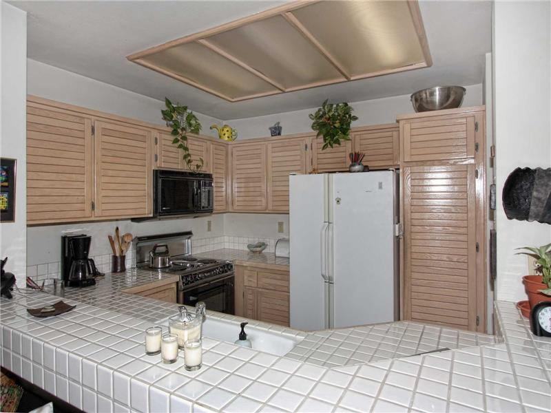The open kitchen has oak cabinetry, ceramic tiled counter tops and a jenn-aire range/oven