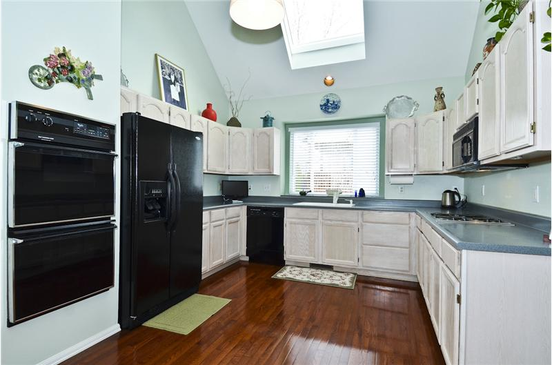 Kitchen w/wood floor, all appliances stay