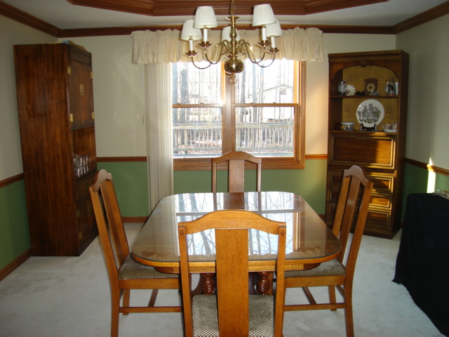 formal dining room with tray ceiling, crown molding, and chair rail
