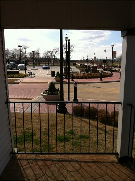 Looking off front porch at public parking lot across street