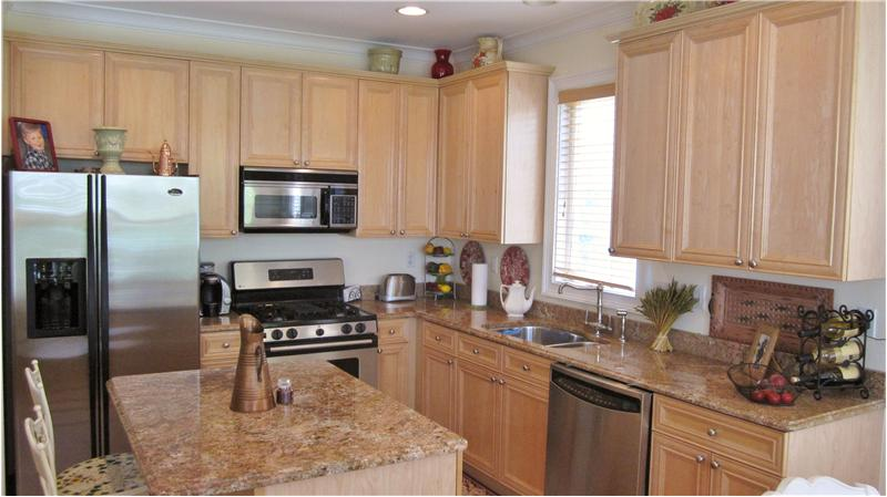 Kitchen with island, granite countertops and stainless steel appliances